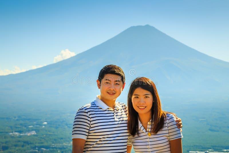 Het openluchtportret van paartoeristen met beroemde Fuji-vulkaanachtergrond stock foto
