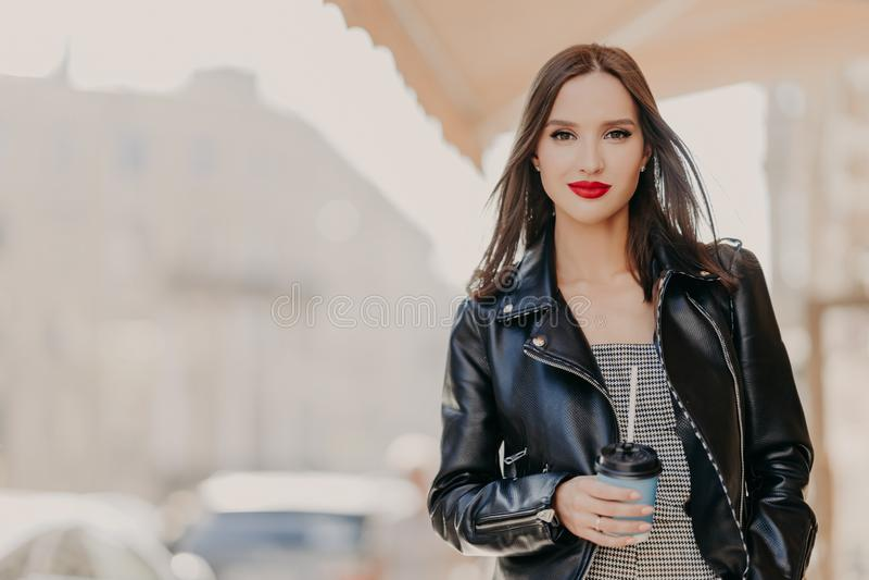 Het openluchtschot van aantrekkelijk millennial vrouwelijk model met make-up, gekleed in modieus leerjasje, drinkt koffie van weg stock foto's