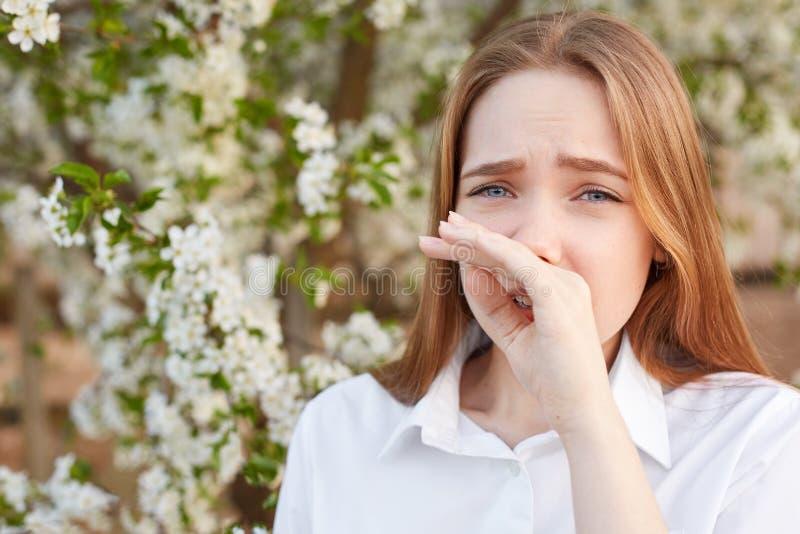 Het openluchtschot van droevig beklemtoond mooi jong wijfje wrijft neus zoals allergie heeft tot bloei te komen, elegant wit over stock foto's