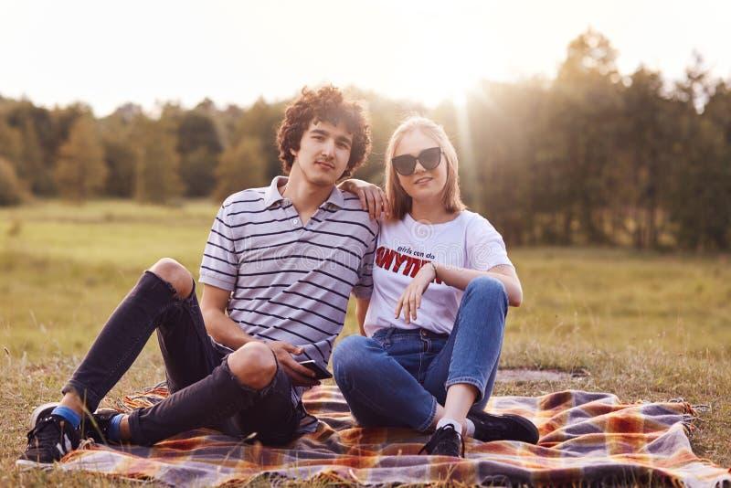 Het openluchtschot van gelukkig romantisch paar heeft datum op aard, zit op plaid, bekijkt vreugdevol camera, stelt tegen mooie z stock fotografie