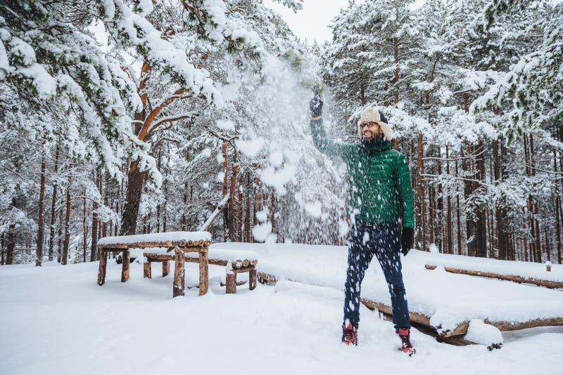 Het openluchtschot van knap gebaard mannetje gekleed in warme kleren, heeft pret zoals werpt sneeuw in lucht, vakantie in de wint stock afbeelding