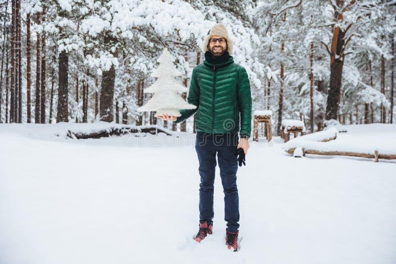 Het openluchtschot van knap mannetje draagt warme hoed en die het groene jasje houdt de winterspar, stelt tegen bomen met sneeuw  royalty-vrije stock foto