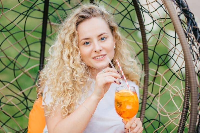 Het openluchtschot van het prettige kijken vrouwelijk met krullend licht haar, dranken verse koude drank, rust in het hangen van  stock foto