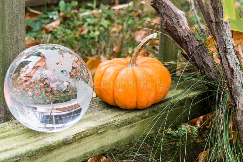 Het openluchtstilleven van het de herfstseizoen met pompoen en glasbol stock afbeeldingen