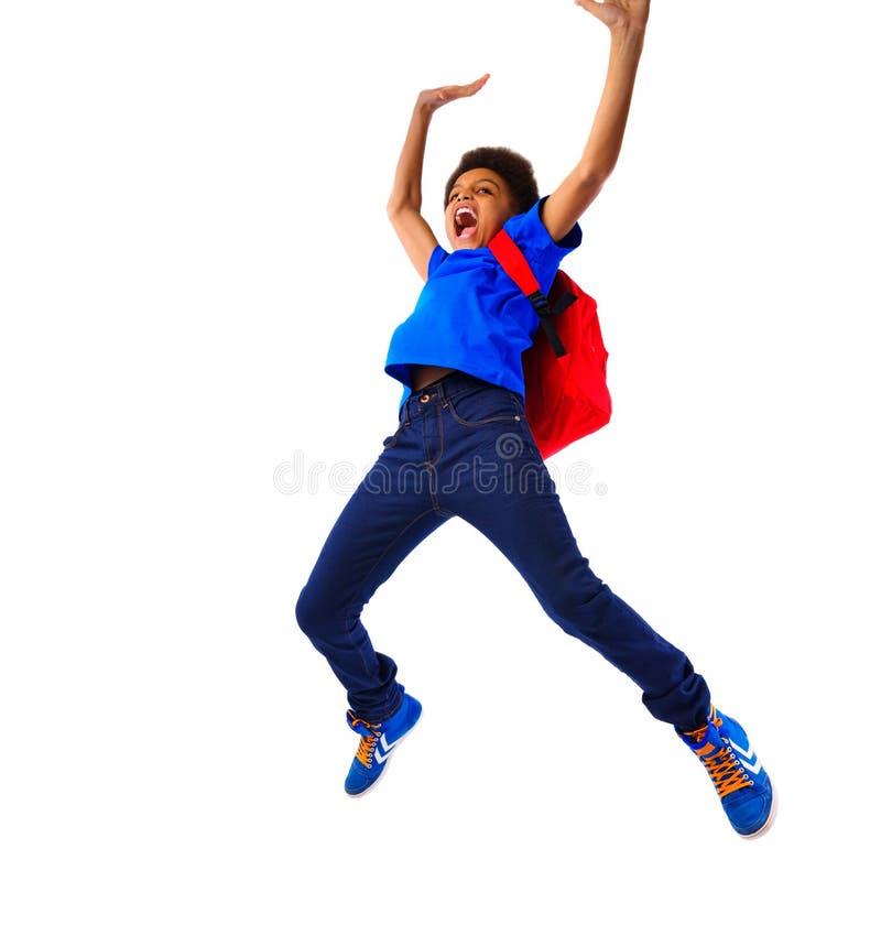Het opgewekte Afrikaanse Amerikaanse schooljongen springen royalty-vrije stock afbeelding