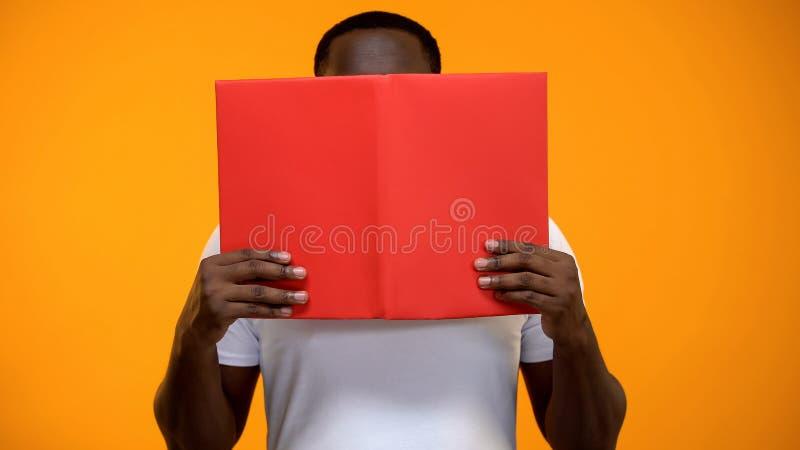 Het opgewekte Afro-Amerikaanse boek van de mensenlezing, het bestuderen en zelfontplooiing, close-up royalty-vrije stock foto