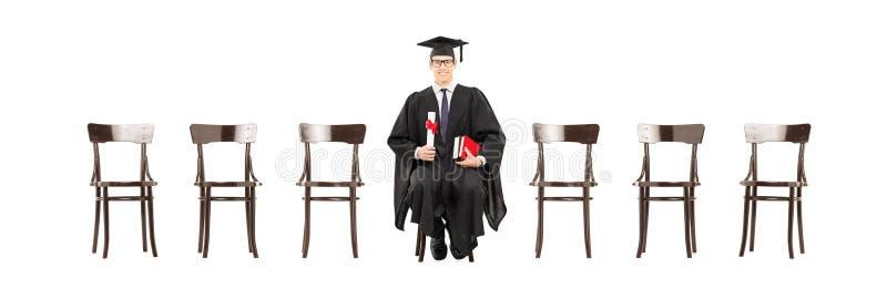 Het opgewekte diploma van de studentholding, gezet op houten stoel stock afbeelding