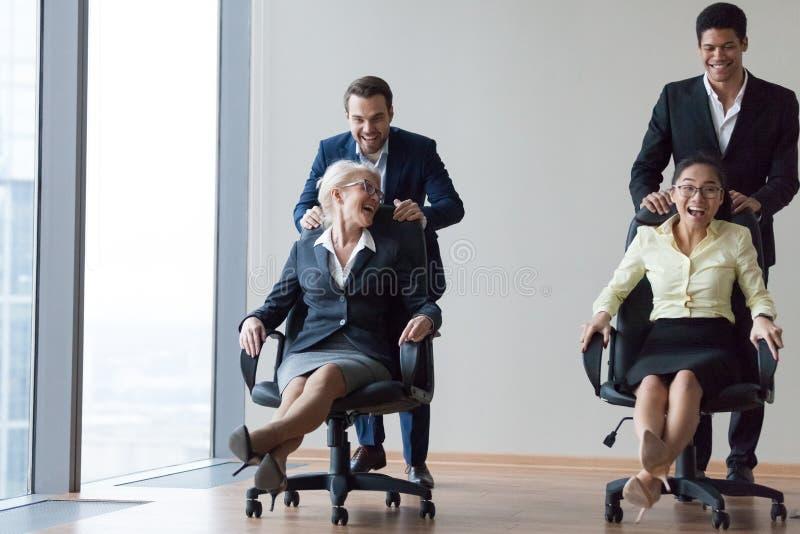 Het opgewekte diverse werknemers het lachen berijden op stoelen in bureau royalty-vrije stock afbeelding
