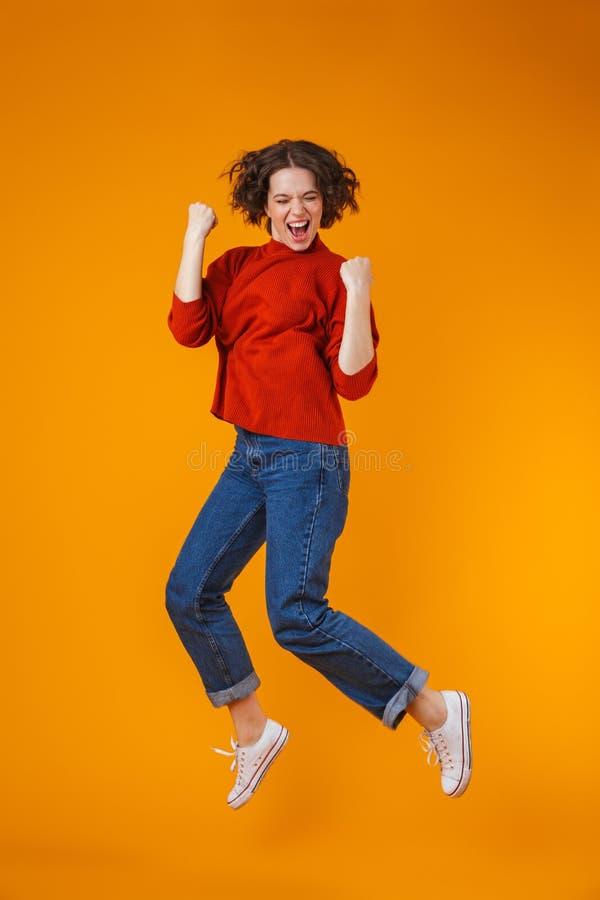 Het opgewekte emotionele gelukkige jonge mooie vrouw stellen geïsoleerd over gele muurachtergrond stock afbeelding