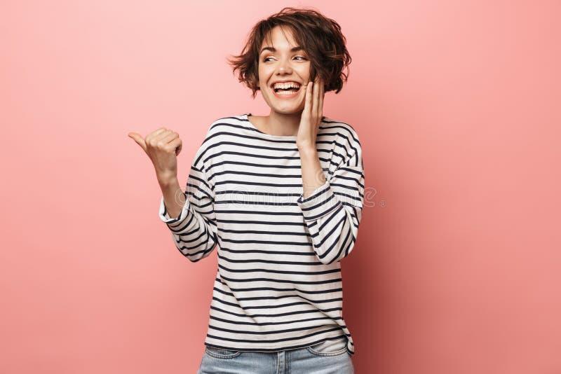 Het opgewekte geschokte verraste mooie vrouw stellen geïsoleerd over het roze muur richten als achtergrond stock foto's
