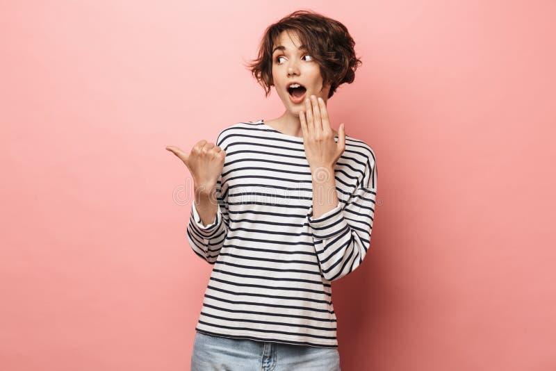 Het opgewekte geschokte verraste mooie vrouw stellen geïsoleerd over het roze muur richten als achtergrond stock afbeeldingen