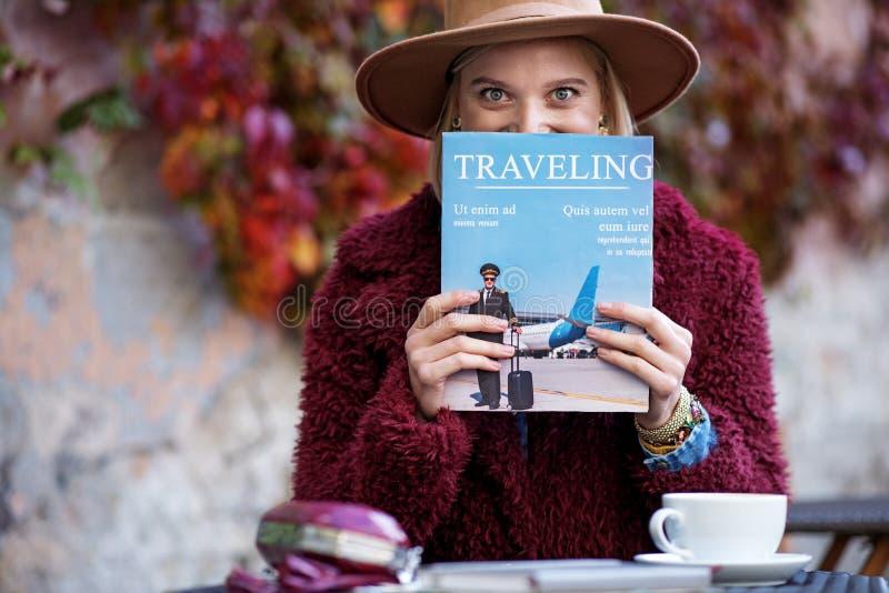 Het opgewekte jonge dagboek van de vrouwenlezing over reizen stock foto's