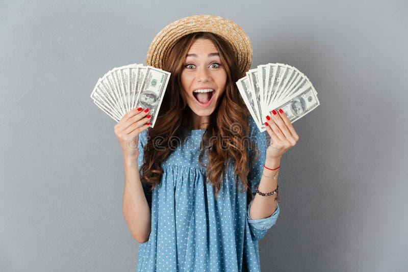 Het opgewekte jonge gelukkige geld van de vrouwenholding kijkend camera stock foto