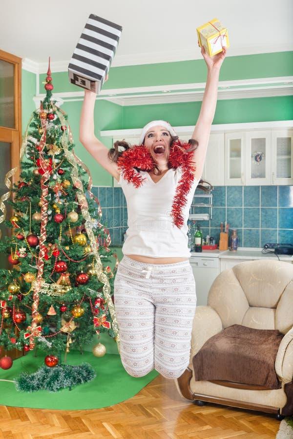 Het opgewekte jonge vrouw springen van vreugde met giften in handen stock afbeeldingen