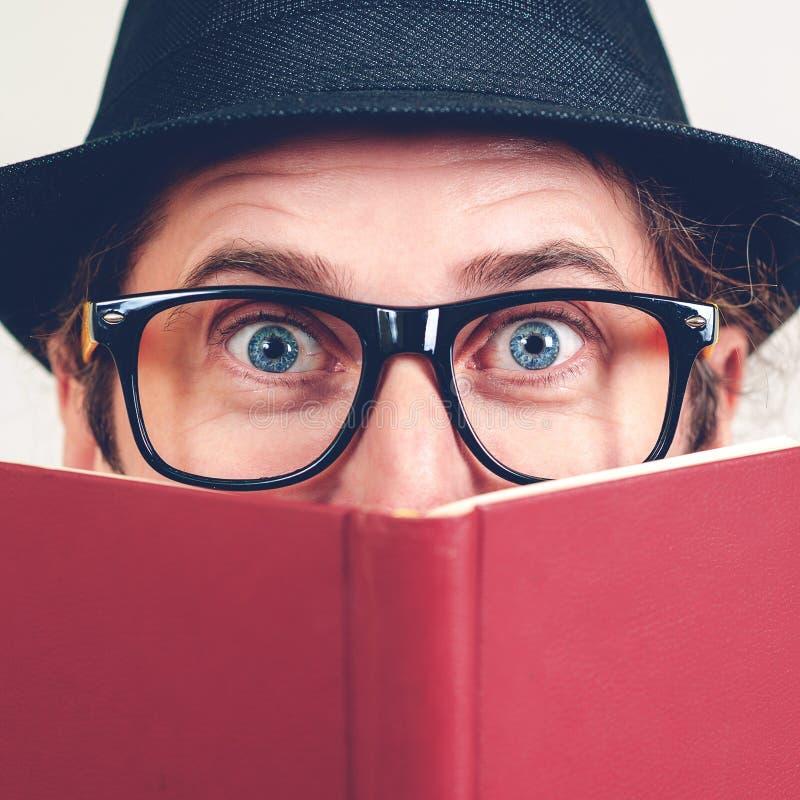 Het opgewekte nerd verbergen achter boeken Speelse gelukkige jonge mens die in grappige glazen en uitstekende hoed een boek houde stock fotografie