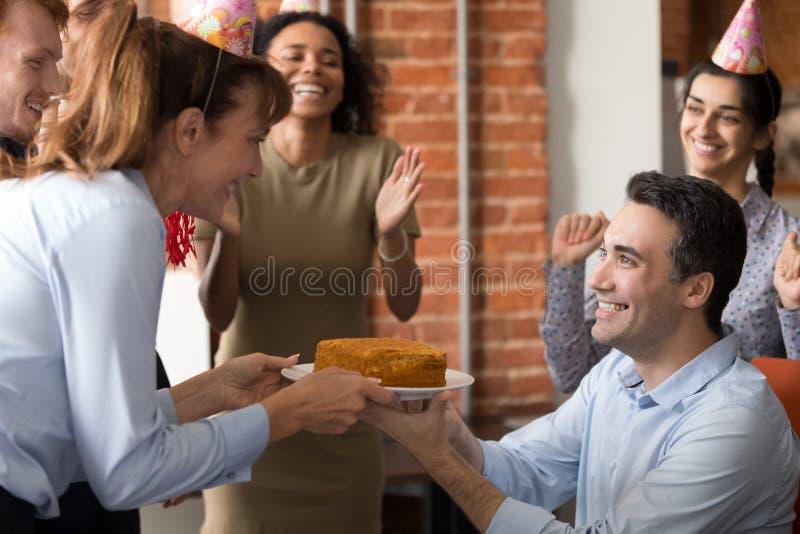 Het opgewekte team wenst collega die in bureau geluk verjaardagsgeschenk maken stock afbeelding