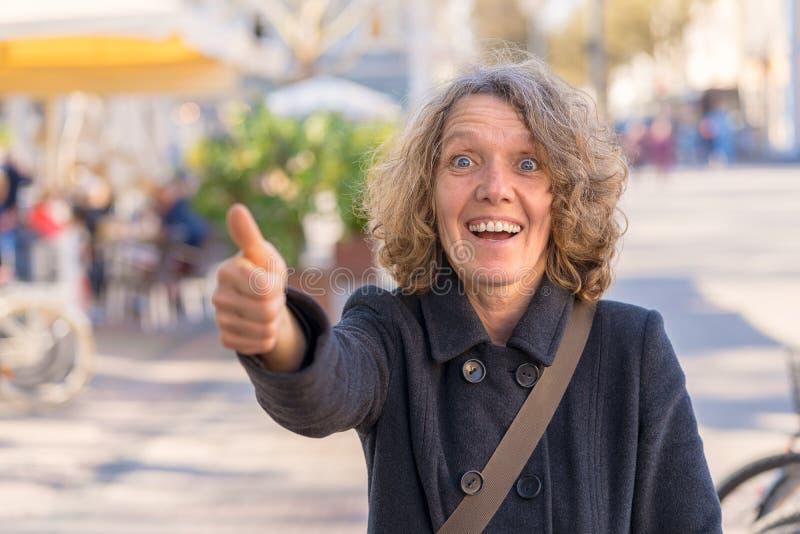 Het opgewekte verbaasde vrouw geven duimen omhoog royalty-vrije stock afbeeldingen