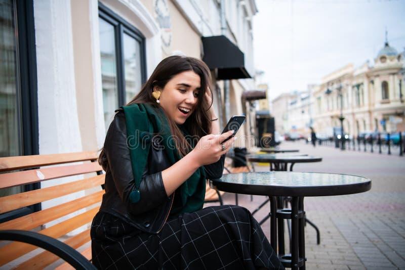 Het opgewekte verbazende nieuws van de vrouwenlezing online in een smartphone bij de straatkoffie royalty-vrije stock foto's