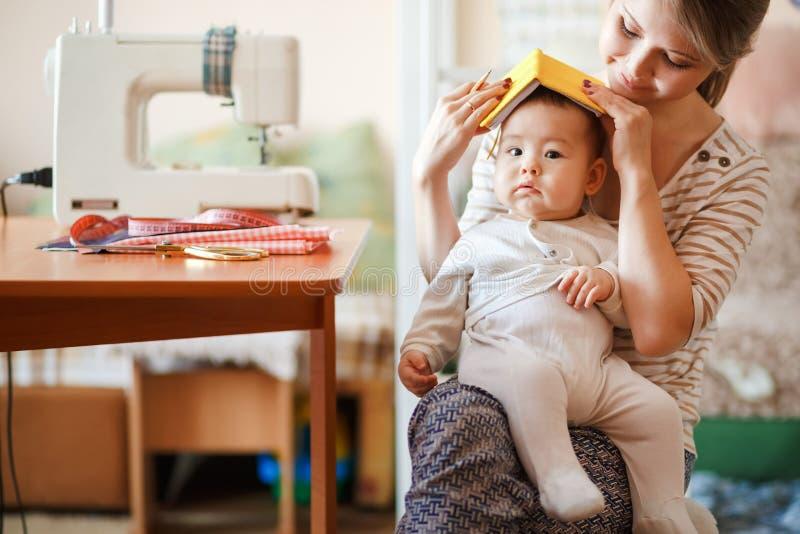 Het opheffen van kinderen, kinderverzorging, babysitter Moeder en zuigeling die thuis rol-spelende spelen spelen Leuk pretoudersc stock afbeeldingen