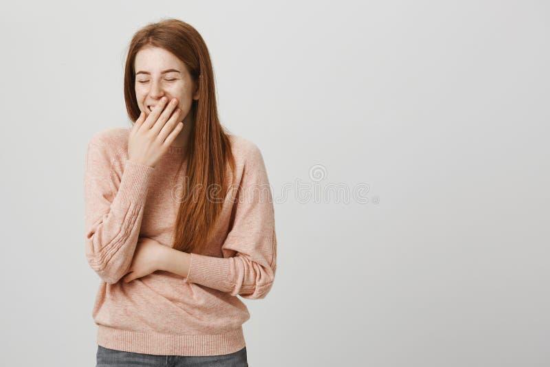 Het oprechte aanbiddelijke roodharige Kaukasische vrouw luid lachen uit terwijl het behandelen van mond met hand, die in goede st royalty-vrije stock afbeeldingen
