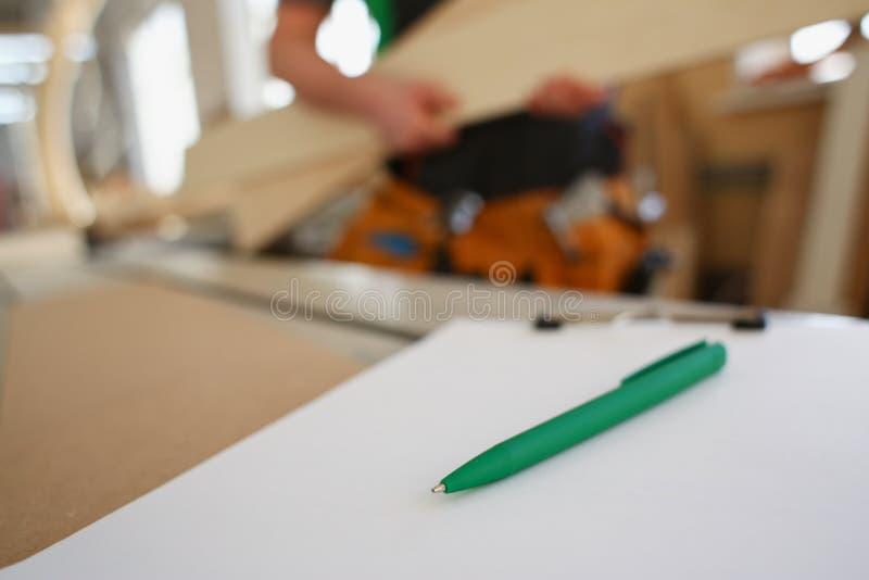 Het opstellen van groene pen die op bureau op klembord liggen stock afbeelding