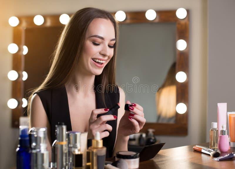 Het optimistische meisje houdt make-upproduct royalty-vrije stock foto