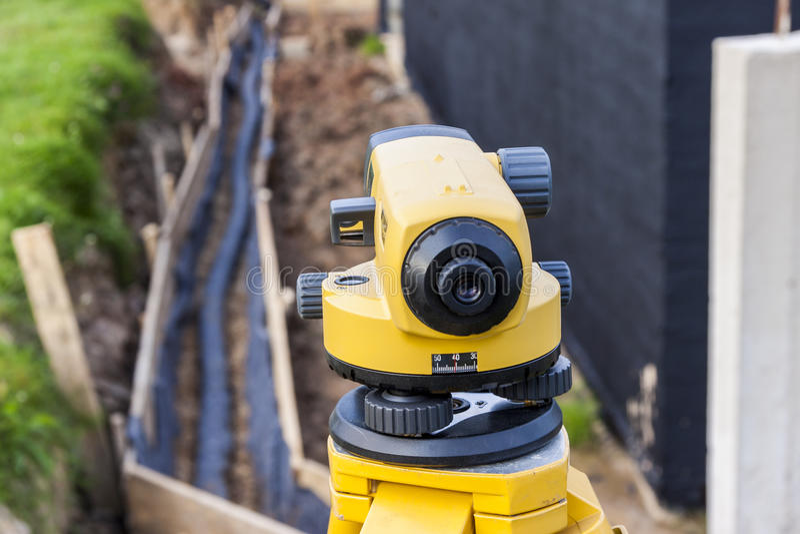 Het optische niveau van het landmetersmateriaal bij bouwwerf stock fotografie