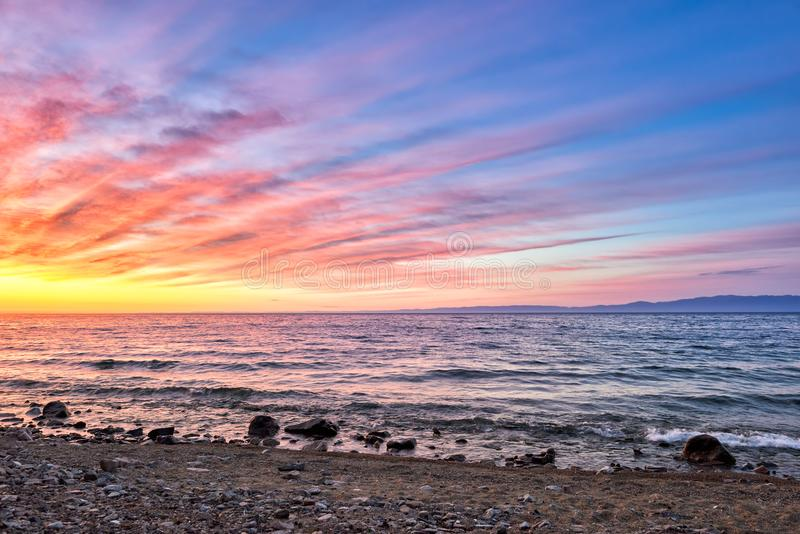 Het opvlammen de dageraad is op oppervlakte van Meer Baikal stock afbeelding