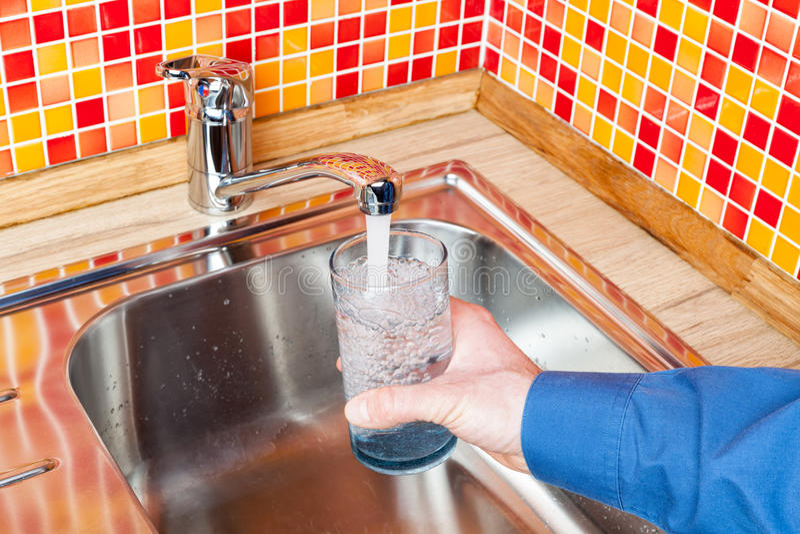 Het opvullen van een glas met water van keukenkraan POV stock fotografie