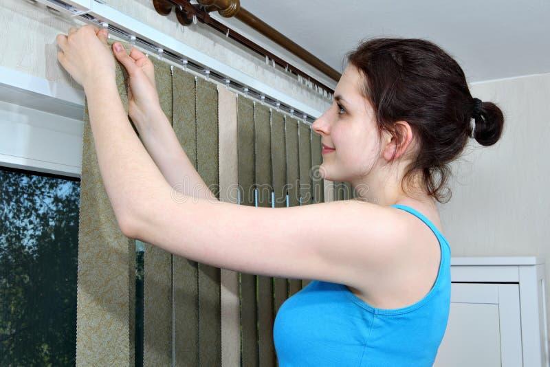 Het opzetten de blinden, de latjes van de stoffenzonneblinden van de Meisjeshaak, installeren zonneblinden stock afbeeldingen