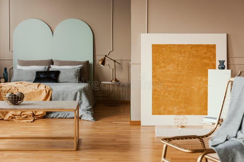 Het oranje abstracte schilderen in modieuze slaapkamer met blauwe bladen stock afbeeldingen