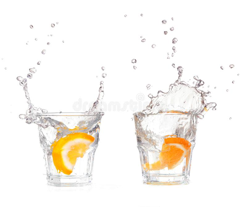 Het oranje bespatten in glas water op wit stock foto's