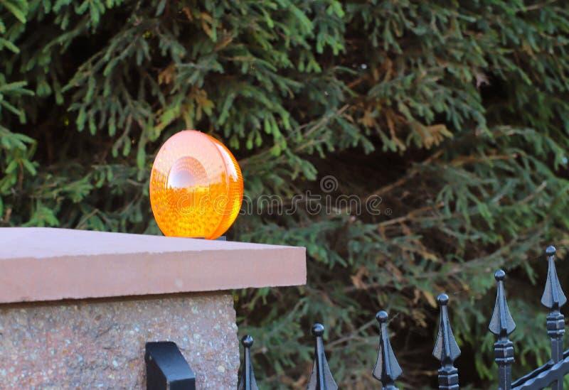 Het oranje die licht van het ruimtealarm op een post de Intercomflatgebouw van de baksteenomheining bij de ingang aan een privé b royalty-vrije stock afbeeldingen