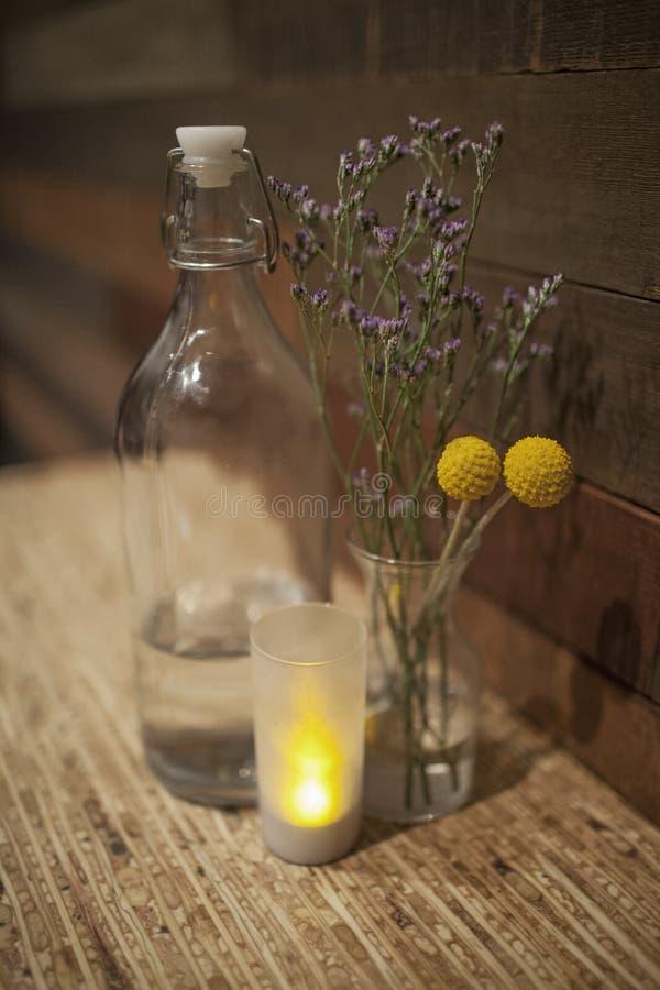 Het oranje en Rode droge madeliefje bloeit in een antieke kruik van het Balglas tussen uitstekende waterfles en kleine kaars op h stock fotografie