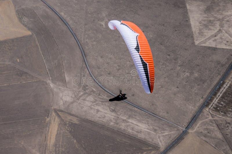 Het oranje en witte glijscherm proef vliegen boven wegdurin royalty-vrije stock afbeelding