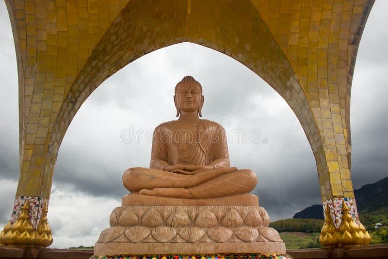 Het oranje marmeren standbeeld van Boedha in meditatie stelt royalty-vrije stock foto