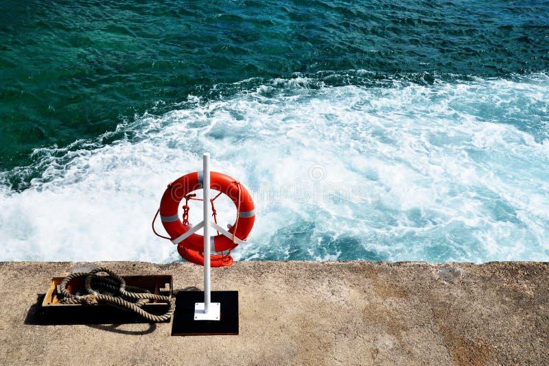Het oranje reddingsboeiring hangen op een pijler en oceaan op achtergrond, hoogste mening, aard overzees landschap met exemplaarr royalty-vrije stock fotografie