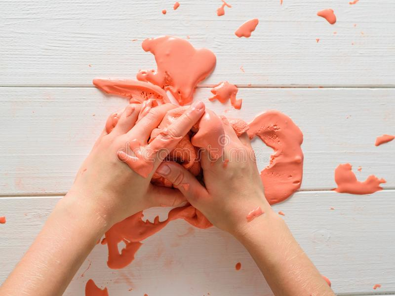 Het oranje slijm spreidt van de handen van een kind op een witte lijst uit royalty-vrije stock fotografie