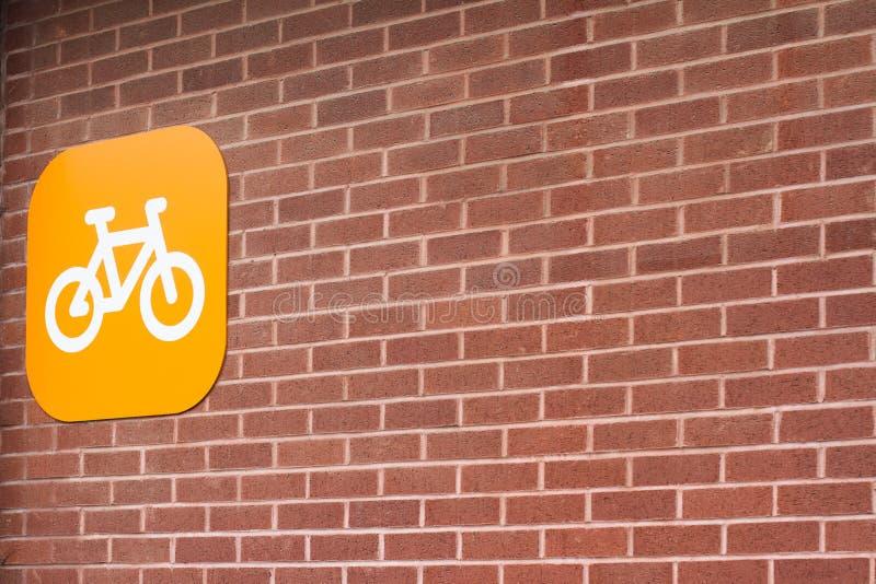 Het oranje teken van het fietsparkeren op bakstenen muur stock foto