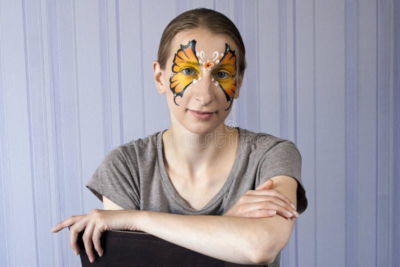Het oranje vlinder facepainting stock afbeeldingen
