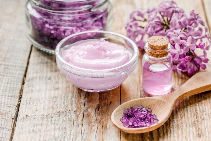 het organische zout, room, uittreksel in lilac schoonheidsmiddel plaatste met bloemen op houten lijstachtergrond royalty-vrije stock fotografie