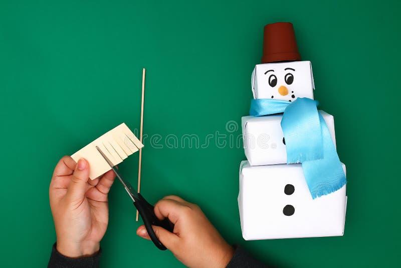 Het originele ontwerp van de drie Kerstmisgift van Witboek, een satijnlint in de vorm van een sneeuwman op een groene achtergrond stock afbeelding
