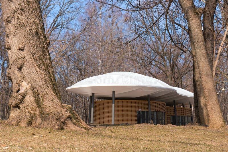 Het originele het winkelen paviljoen in het stadspark op de achtergrond van geweven boomboomstam Stedelijk Landschap De lente royalty-vrije stock foto