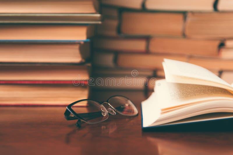 Het oude boek in bibliotheek met open handboek, stapelstapels van het archief van de literatuurtekst op lezingsbureau in school b stock foto's