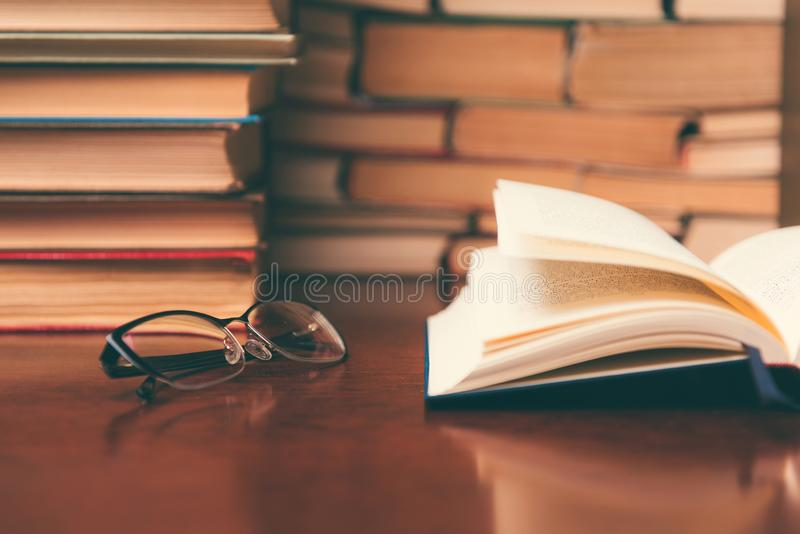 Het oude boek in bibliotheek met open handboek, stapelstapels van het archief van de literatuurtekst op lezingsbureau in school b stock foto