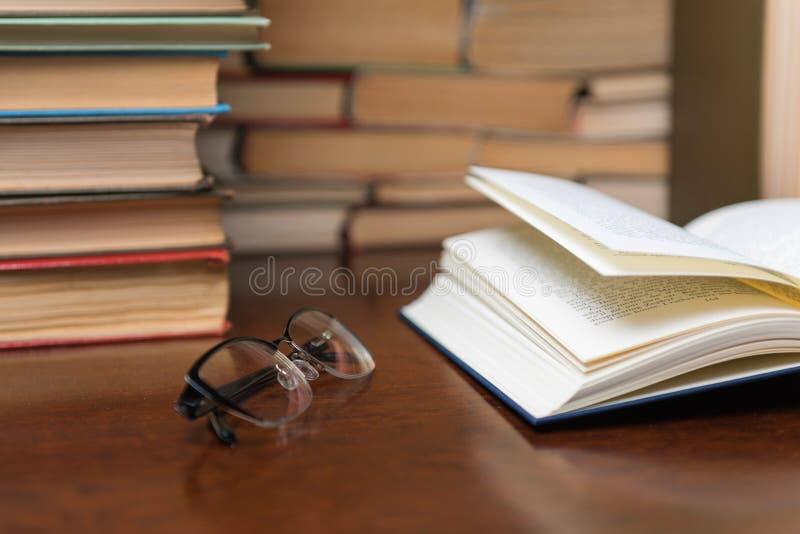Het oude boek in bibliotheek met open handboek, stapelstapels van het archief van de literatuurtekst op lezingsbureau in school b royalty-vrije stock afbeeldingen