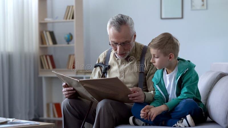 Het oude boek van de mensenlezing aan kleinzoon, die ervaring geven aan jongerengeneratie royalty-vrije stock foto