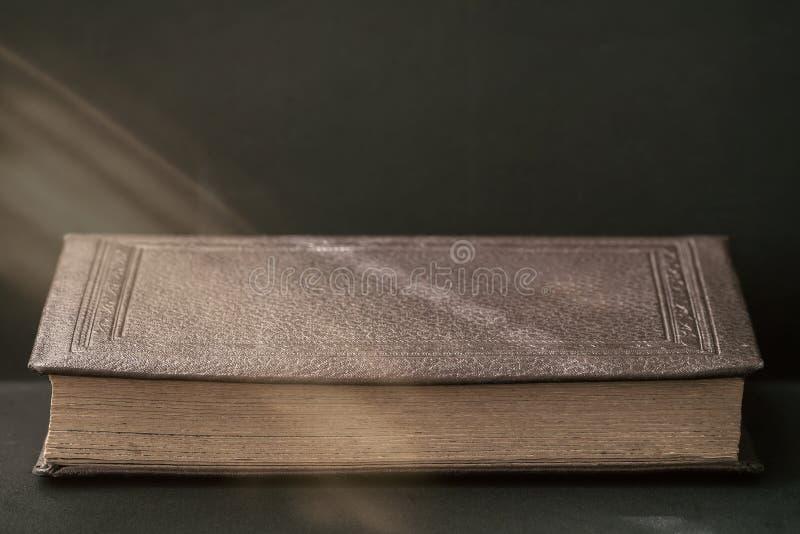 Het oude boekclose-up onder zonnestraal op een donkere achtergrond, kopieert ruimte, uitstekende, rustieke stijl Lezingstijd, ter stock fotografie
