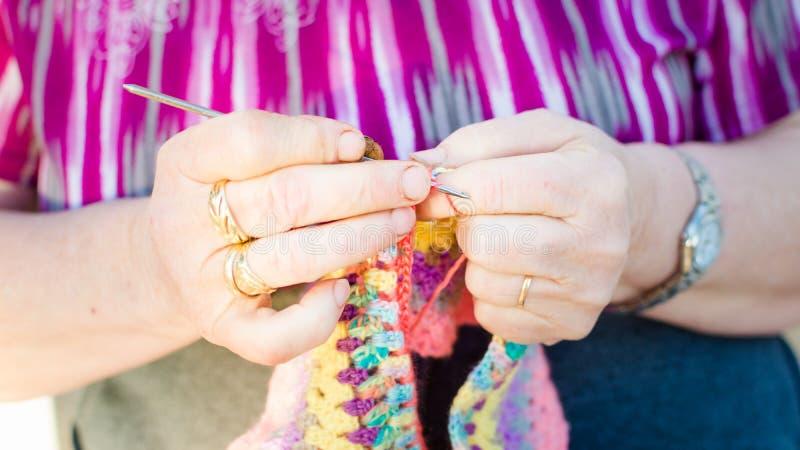 Het oude dame breien op breinaalden, die kleurrijke wol gebruiken royalty-vrije stock foto