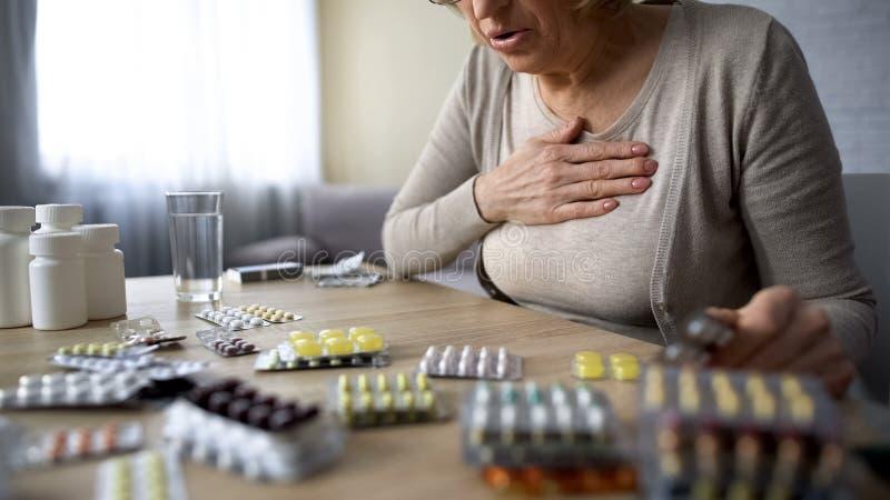 Het oude dame onwel voelen, zoekend pillen, zieke vrouw die hart aan probleem lijden royalty-vrije stock foto